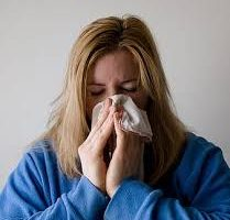 Woman with respiratory illness or allergies blowing her nose.