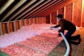 Loose-fill insulation being blown-in over batt insulation